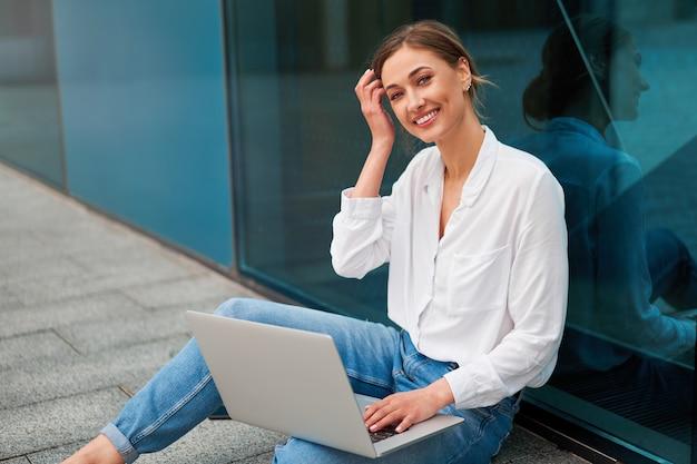 Pessoa de negócios mulher bem sucedida mulher de negócios ao ar livre com laptop celular
