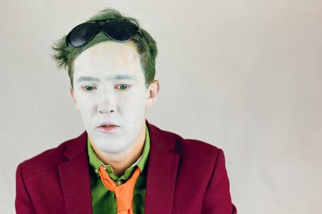 Pessoa de terno com gravata de listras amarelas olha para baixo ator com maquiagem branca no rosto e olhos verdes e ...