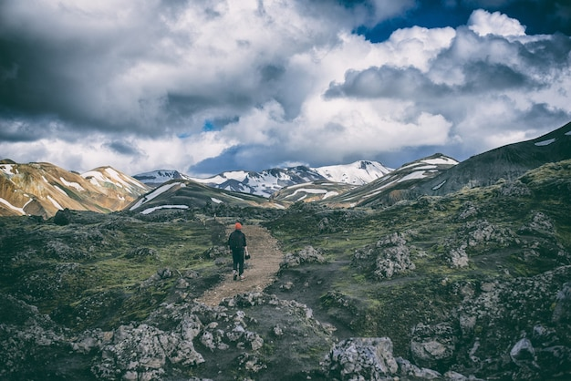 Pessoa de terno preto caminhando na estrada marrom