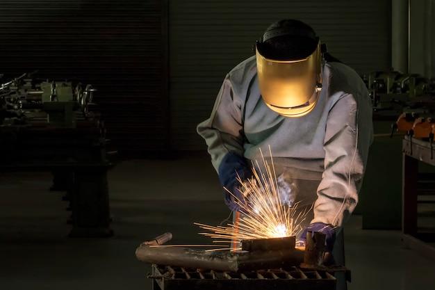 Pessoa de trabalho industrial no aço do soldador da fábrica