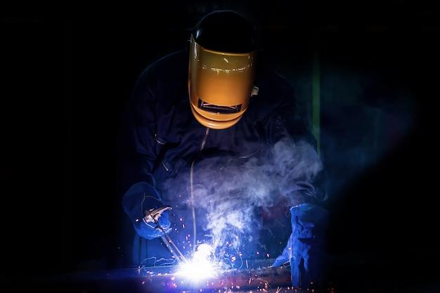 Pessoa de trabalho sobre o aço do soldador usando a máquina de soldadura elétrica.