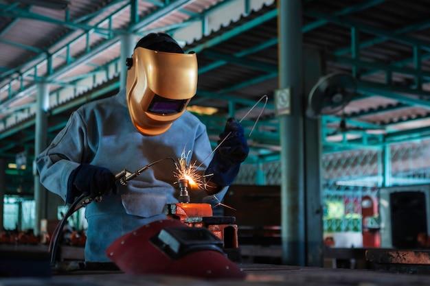 Pessoa de trabalho sobre o aço do soldador usando a máquina de soldadura elétrica