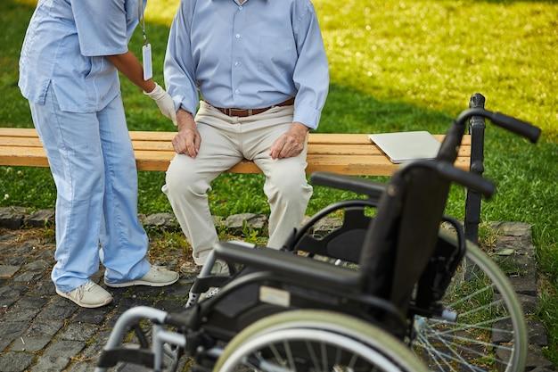 Pessoa de uniforme segurando a mão do paciente para se levantar