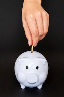 Pessoa de visão frontal colocando uma moeda em um cofrinho