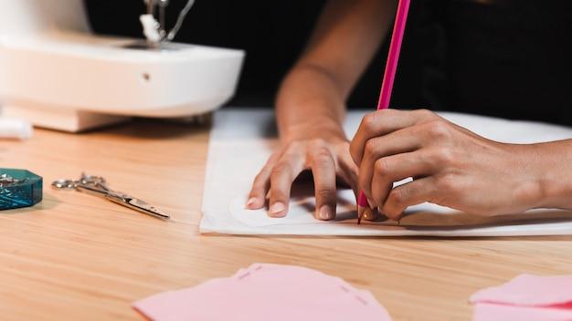 Pessoa de vista frontal fazendo um desenho antes de costurar