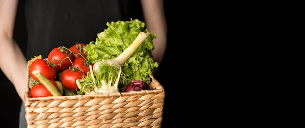 Pessoa de vista frontal segurando cesta com legumes