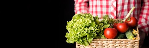 Pessoa de vista frontal segurando legumes para salada