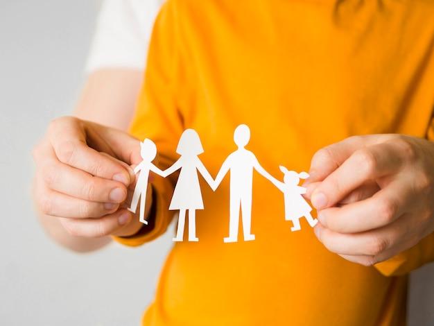 Pessoa de vista frontal segurando papel de família