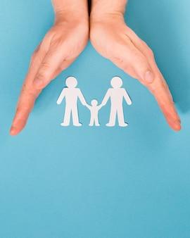 Pessoa de vista superior, segurando nas mãos bonito papel família com espaço de cópia