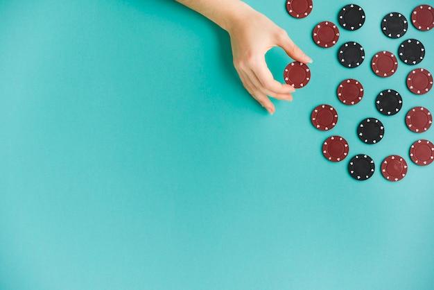 Pessoa de vista superior segurando uma ficha de poker