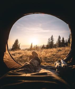 Pessoa deitada em uma barraca apreciando a bela vista do pôr do sol