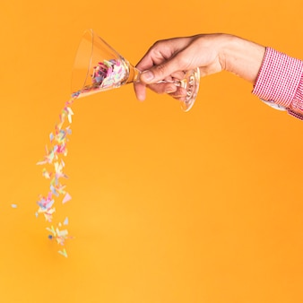 Pessoa, derramando confete de um copo