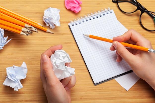 Pessoa, desenho em um bloco de notas e material de escritório em cima da mesa