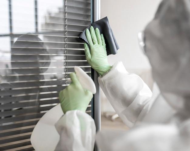 Pessoa desinfetando uma área perigosa enquanto usa um traje de proteção
