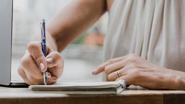 Pessoa digitando com uma caneta no caderno
