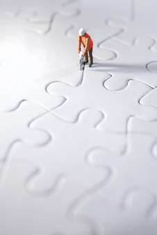 Pessoa diminuta que constrói enigmas, abrindo caminho para a equipe e conceito de trabalho. conceito de esforço