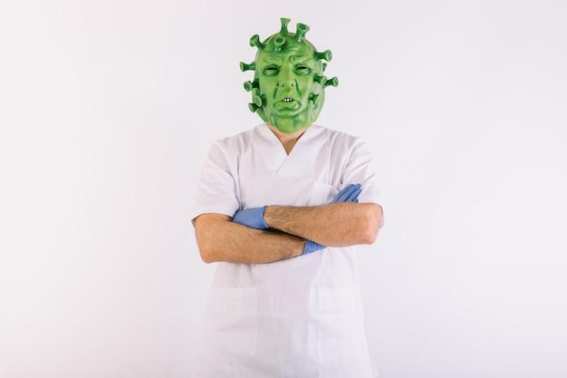 Pessoa disfarçada de coronavírus com vírus covid19 de máscara de látex, vestindo terno de médicos com os braços cruzados sobre fundo branco.