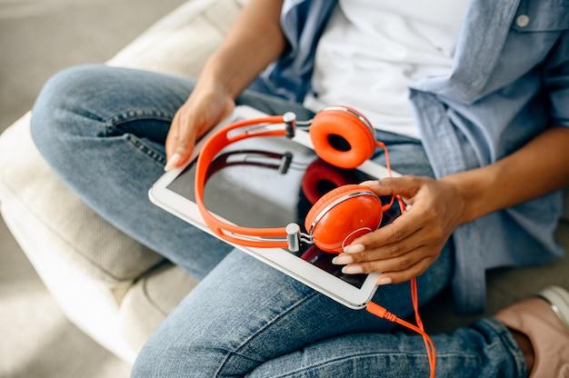 Pessoa do sexo feminino com fones de ouvido e tablet pc sentado na cadeira. linda senhora com fones de ouvido relaxando na sala, amante do som descansando