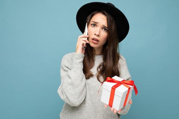 Pessoa do sexo feminino isolada sobre a parede de fundo azul usando elegante chapéu preto e suéter cinza segurando uma caixa de presente falando no smartphone e olhando para a câmera.