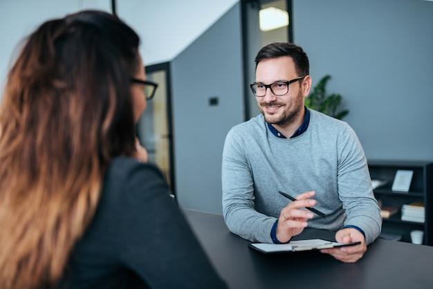 Pessoa do sexo feminino ter uma entrevista de emprego com um recrutador masculino.