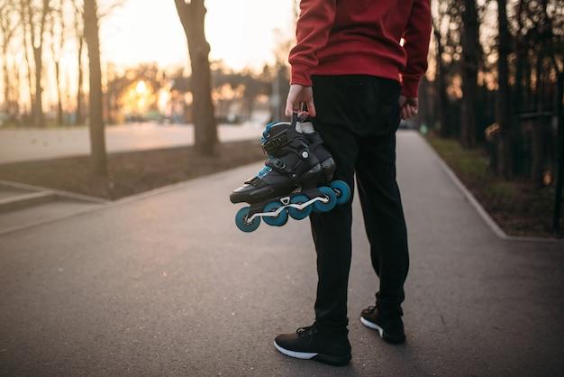 Pessoa do sexo masculino com as mãos com patins, parque da cidade. patins masculinos com patins