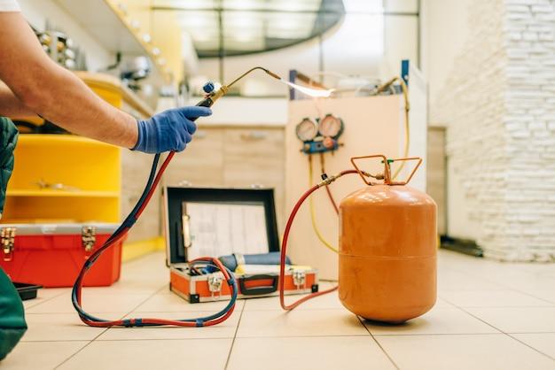 Pessoa do sexo masculino com as mãos com queimador repara a geladeira em casa. reparação de ocupação de frigoríficos, serviço profissional