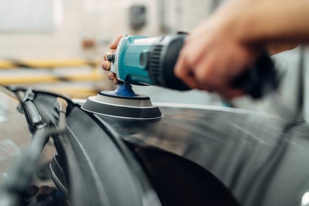 Pessoa do sexo masculino com máquina de polir limpa carro.