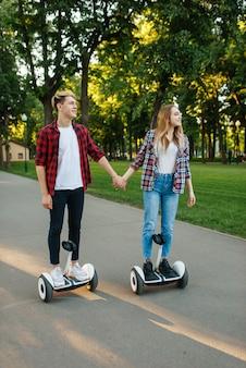 Pessoa do sexo masculino e feminino andando na placa do giroscópio no parque.