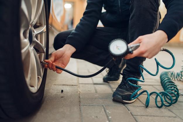Pessoa do sexo masculino verifica a pressão dos pneus