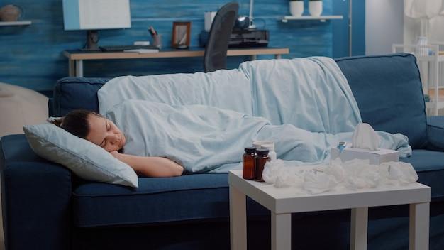 Pessoa doente com náusea dormindo enrolada em um cobertor