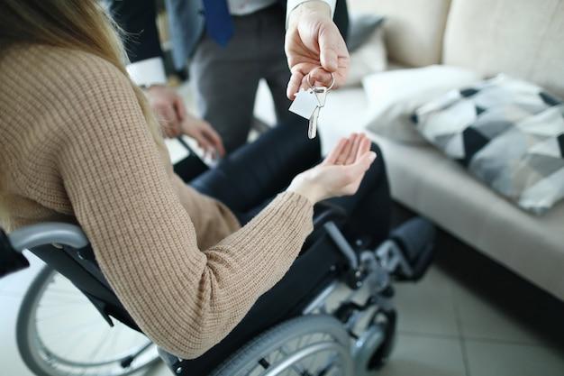 Pessoa em cadeira de rodas, recebendo ajuda, chaves