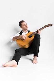 Pessoa em fundo branco, tocando violão