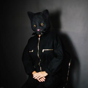 Pessoa em máscara de gato sentado