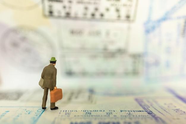 Pessoa em miniatura de empresário com bagagem em pé no passaporte com carimbo da imigração