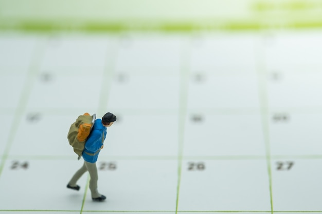 Pessoa em miniatura de viajante com mochila caminhando no calendário