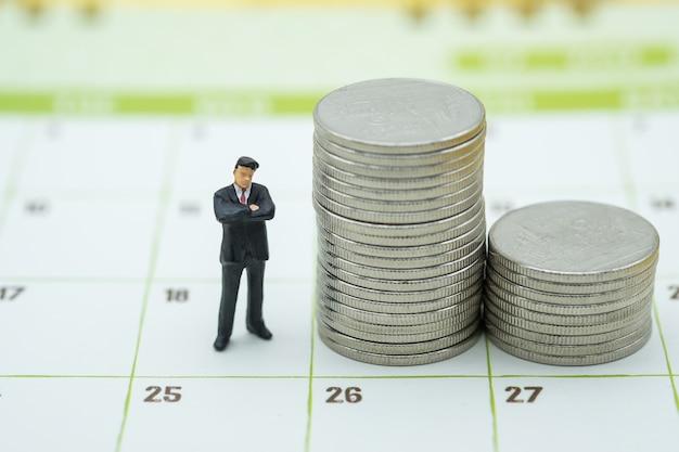 Pessoa em miniatura do empresário em pé com uma pilha de moedas no calendário