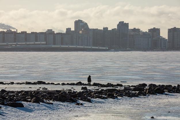 Pessoa em pé na costa do mar gelado do golfo da finlândia, em frente a um distrito com arranha-céus no inverno de são petersburgo, rússia.