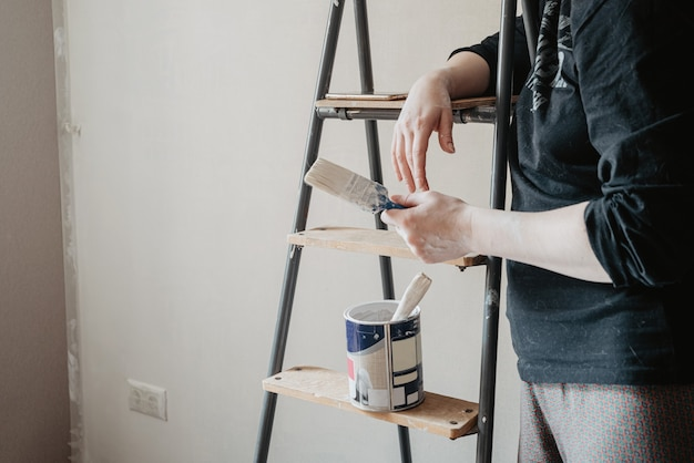 Pessoa em pé perto de uma escada segurando um pincel na mão