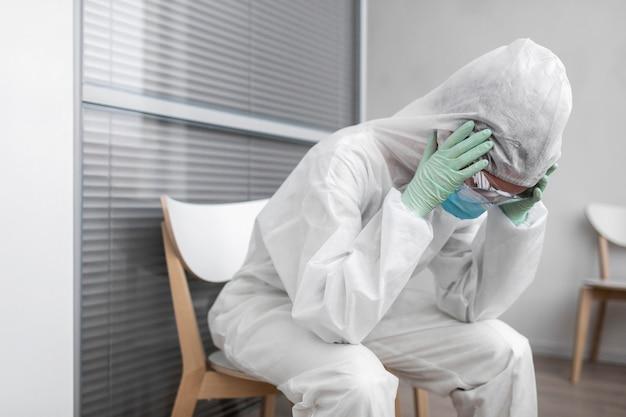 Pessoa em traje de proteção com dor de cabeça