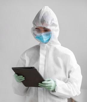 Pessoa em traje de proteção olhando para um tablet
