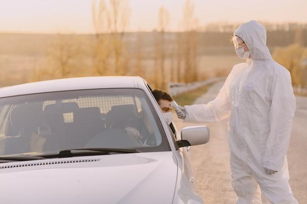 Pessoa em traje de proteção verifica a temperatura