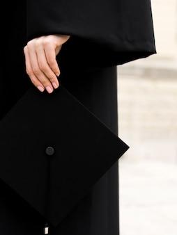 Pessoa em vestido de formatura, segurando seu boné