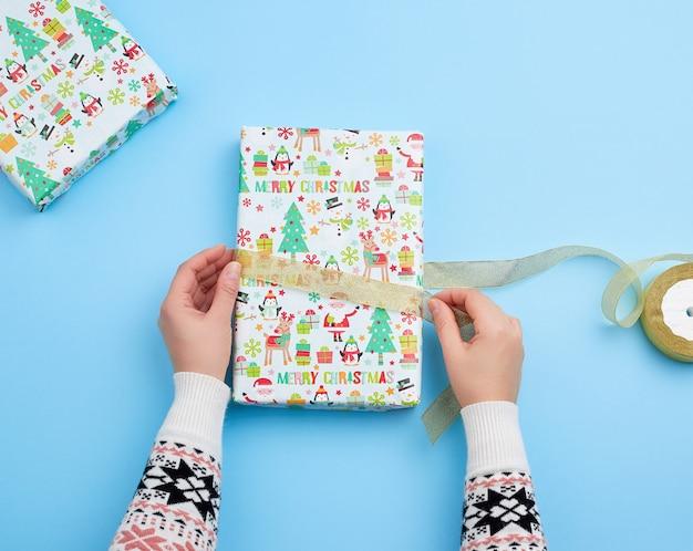 Pessoa, embrulhar um presente em papel de férias em uma superfície azul
