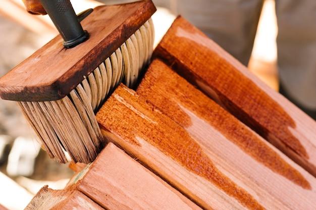 Pessoa envernizando a madeira com pincel grande