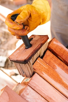 Pessoa envernizando a madeira