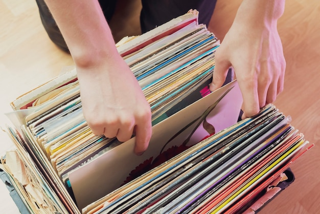 Pessoa escolhe caixa de discos de vinil escavando coleção b