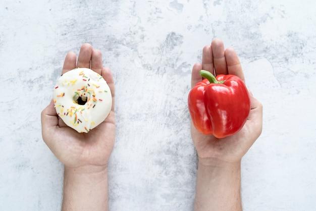 Pessoa escolhendo entre bellpepper e donut sobre o plano de fundo texturizado