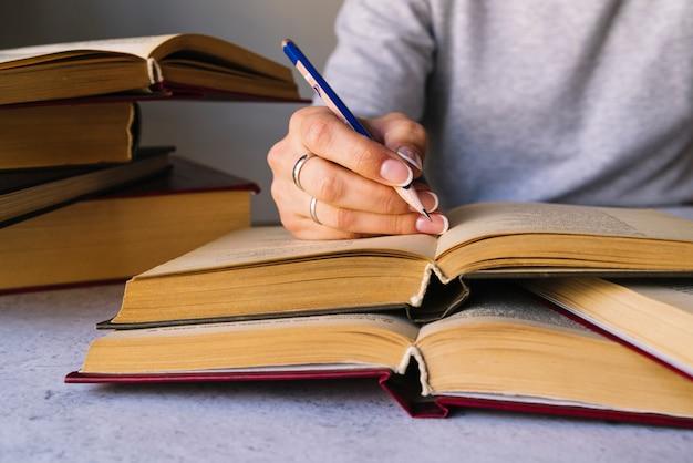 Pessoa escrevendo ao lado da pilha de livro