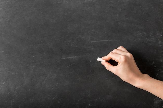 Pessoa escrevendo com giz em uma lousa vazia