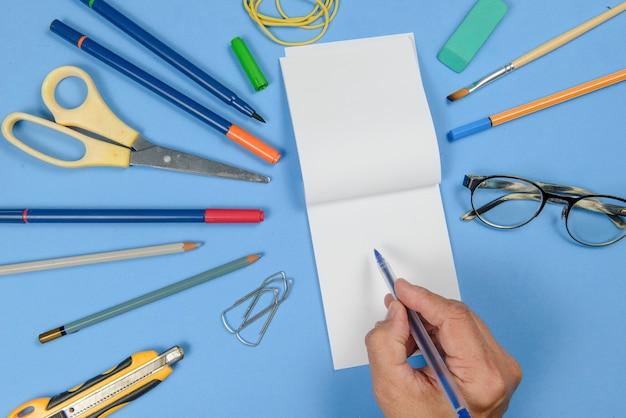 Pessoa escrevendo em itens de caderno